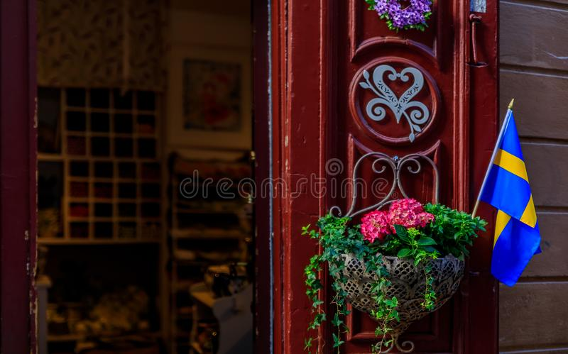 Utsmyckad röd dörr som dekoreras med en svensk flagga och en blomkruka I royaltyfri bild