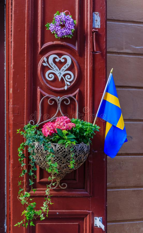 Utsmyckad röd dörr som dekoreras med en svensk flagga och en blomkruka I royaltyfri fotografi