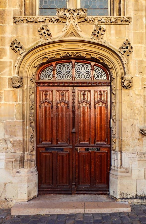 Utsmyckad träingång för dubbel dörr till en gammal kyrka arkivfoto