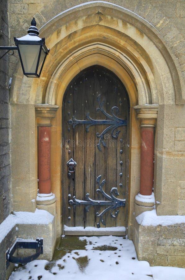 Utsmyckad träkyrklig dörr med snö på jordningen royaltyfria foton