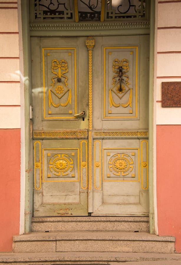 Utsmyckade gamla gröna trädörrar med gul design Tre stenmoment som upp till leder dörröppningen arkivbilder
