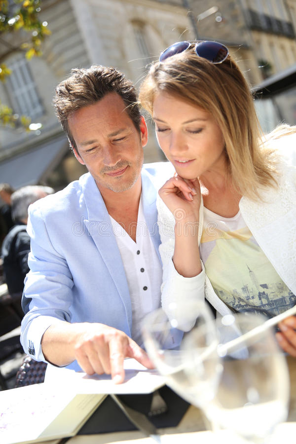 Utsmyckade par som väljer menyn i restaurang royaltyfri bild