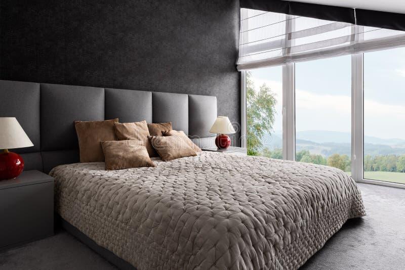 Utsmyckat sovrum med fönsterväggen royaltyfria foton