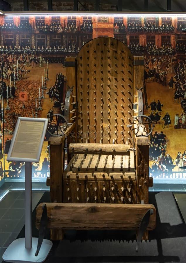 Utställning i tortyrmuseet Bruges - stol av tortyr arkivfoto
