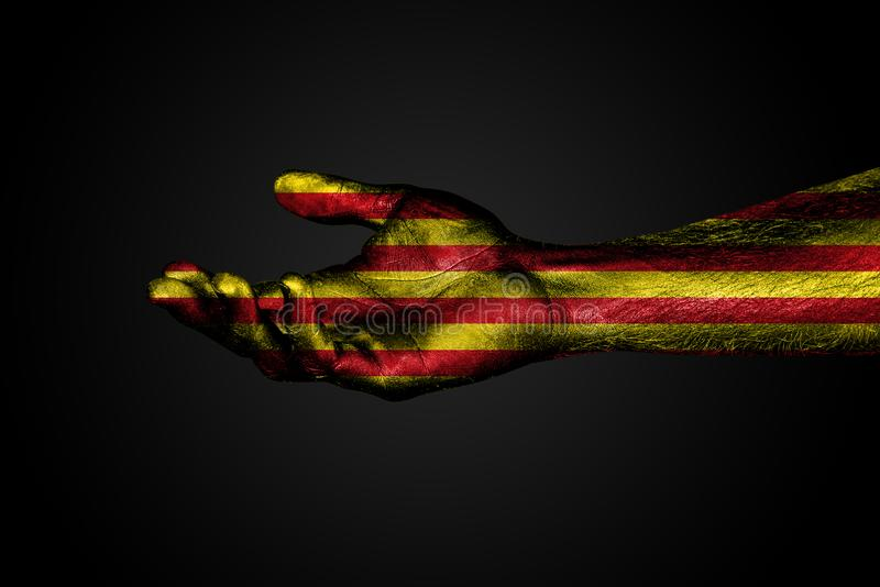 Utsträckt hand med en utdragen Catalonia flagga, ett tecken av hjälp eller förfrågan, på en mörk bakgrund royaltyfria bilder