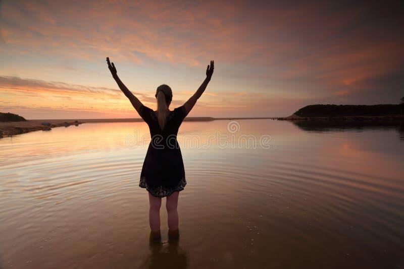 Utsträckta armar för kvinna som lovordar framgång för perfekt dag arkivfoto