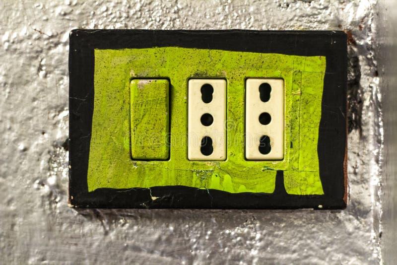Uttag för grön makt i silverfärgvägg royaltyfri fotografi