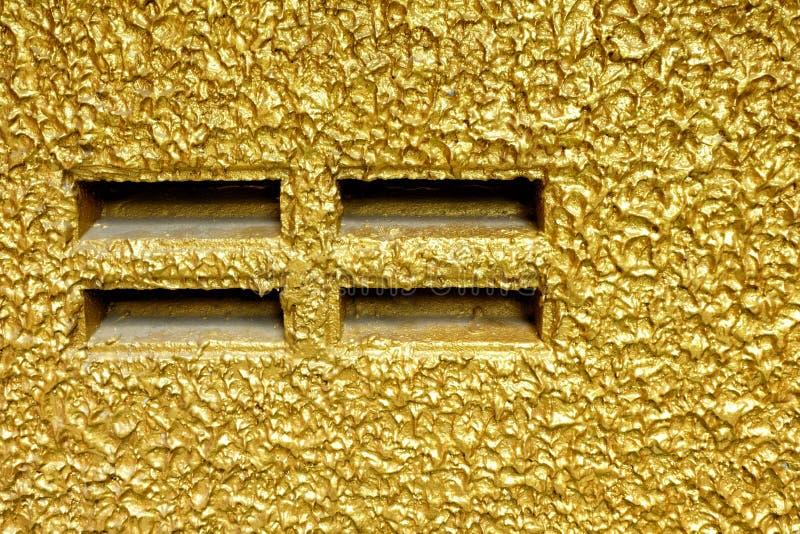 Uttag på den guld- målningbetongväggen arkivfoton