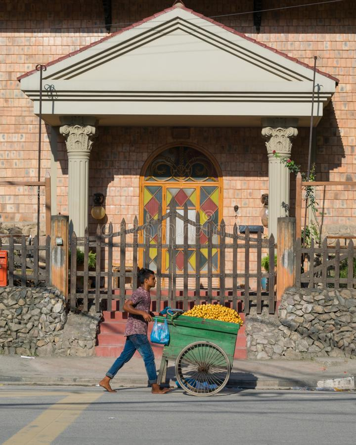 Uttara, Dhaka, Bangladesh - augusti 2019 : En barnvaktare som säljer kinesiskt datum i en skåpbil framför ett regalhus i Uttara. arkivbilder