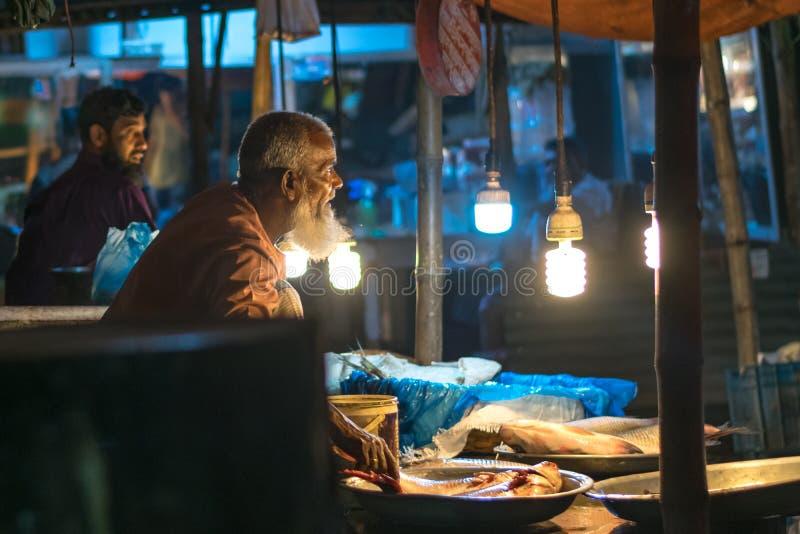 Uttara, Dhaka, Bangladesh - 26 juli 2019 : en gammal man som säljer fisk på den lokala fiskmarknaden i Uttara, Dhaka, Bangladesh royaltyfri foto