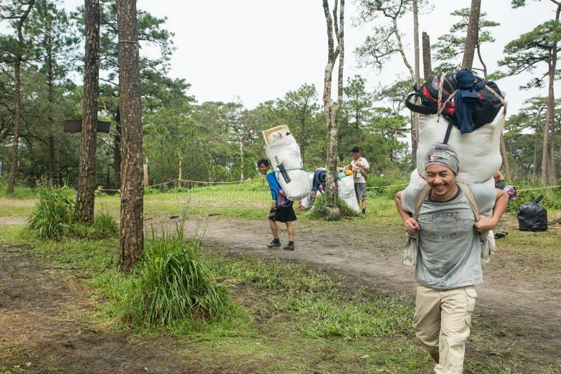 Uttaradit Thailand, 5 AUGUSTI 2018: Arbetare för stark man och mycket bagage på vägen som Trekking på `-berg för ` PHU-SOI-DAO De arkivfoto