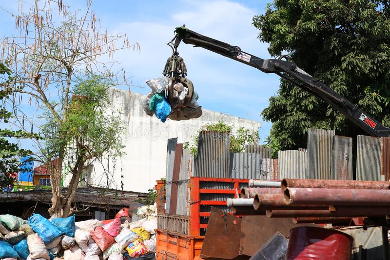 Uttaradit Thailand, Maj 4, 2019 Kranar avskiljer stål- eller rostfritt stålavfalls för återanvändning av global uppvärmningförmin fotografering för bildbyråer