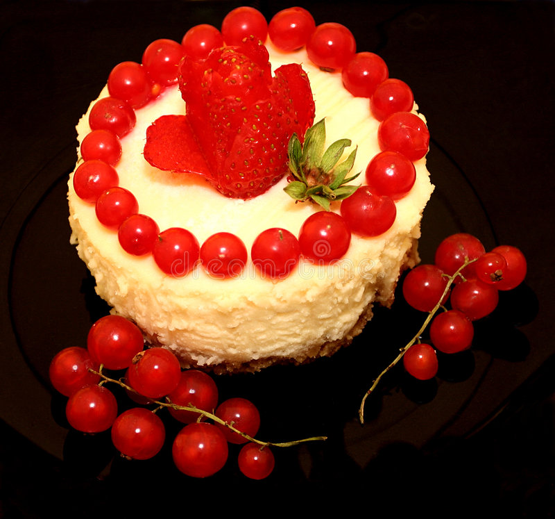 Utterly Delicious Cheesecake. Redcurrant and strawberry cheesecake, resting on black glass, with two small branches of redcurrants next to the cake royalty free stock image
