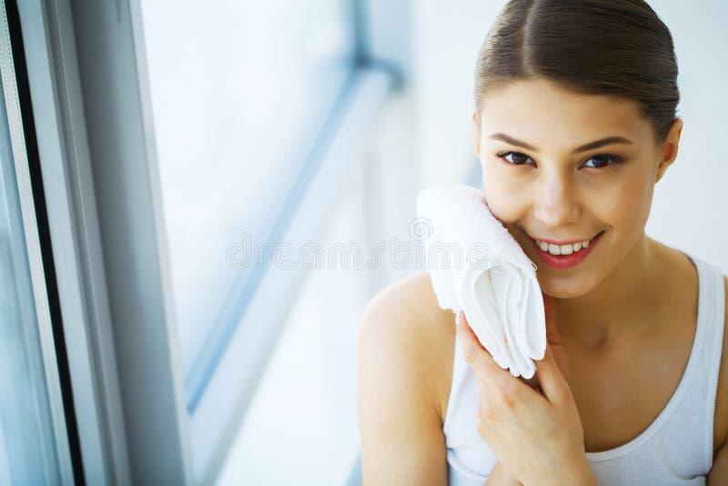 Uttorkning för ung kvinna själv med den vita handduken som ler, stående, arkivfoto
