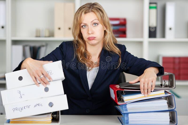 Uttråkad affärskvinna Behind Stacked Binders på skrivbordet arkivbild