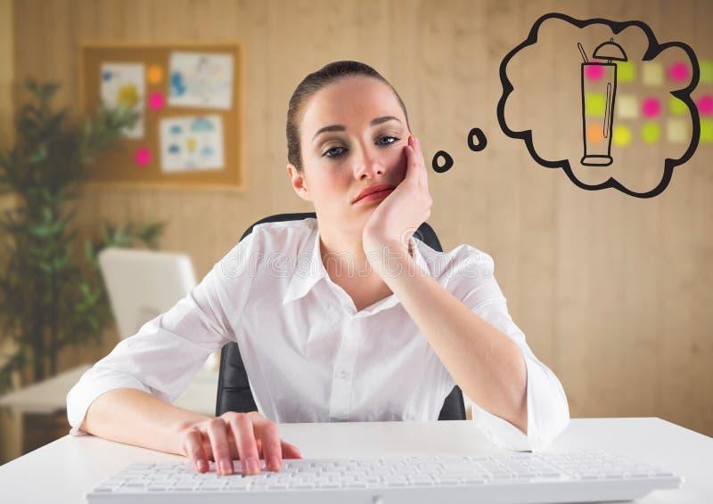 Uttråkad affärskvinna på skrivbordet som drömmer av coctailen mot oskarpt kontor arkivfoto