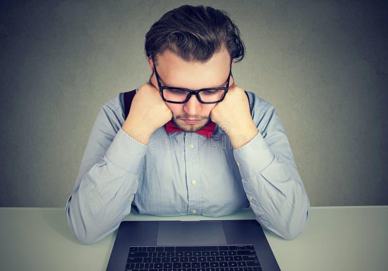 Uttråkad affärsman med inget motivationsammanträde på skrivbordet med bärbara datorn royaltyfria foton