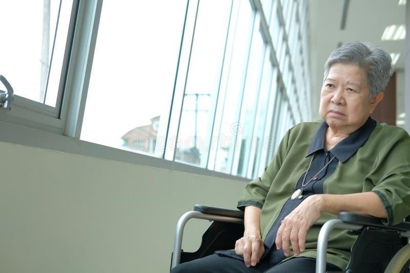 uttråkad deprimerad äldre kvinna i rullstol äldre kvinnlig feelin arkivfoton