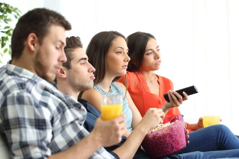 Uttråkad grupp av vänner som hemma håller ögonen på tv royaltyfria bilder