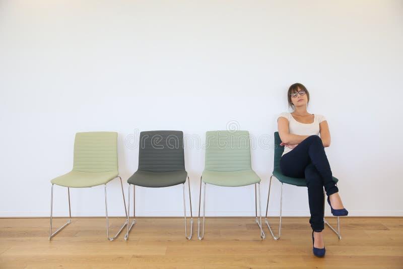 Uttråkad kvinna i väntande rum arkivbilder