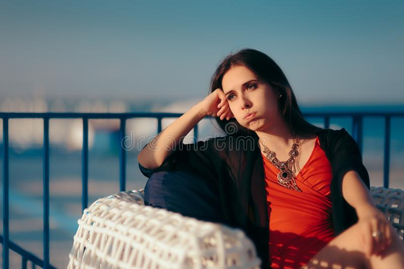 Uttråkad kvinna som känner sig ledsen på sommarferie royaltyfri foto