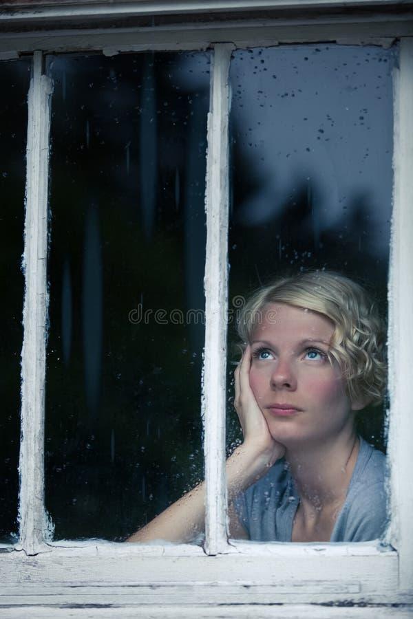 Uttråkad kvinna som ser det regniga vädret vid fönstret fotografering för bildbyråer