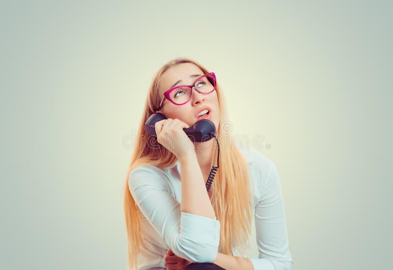 Uttråkad kvinna som talar på telefonen arkivfoto