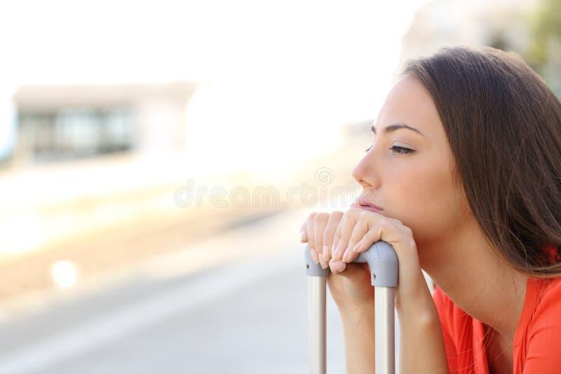 Uttråkad kvinna som väntar på försenat trans. royaltyfri foto