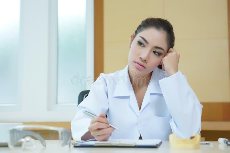 Uttråkad kvinnatandläkare som ser mycket tråkig på hennes skrivbord royaltyfria bilder