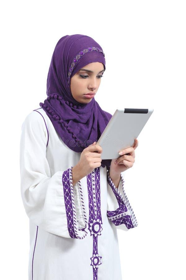 Uttråkad läsning för arabisk kvinna en minnestavlaavläsare arkivfoto