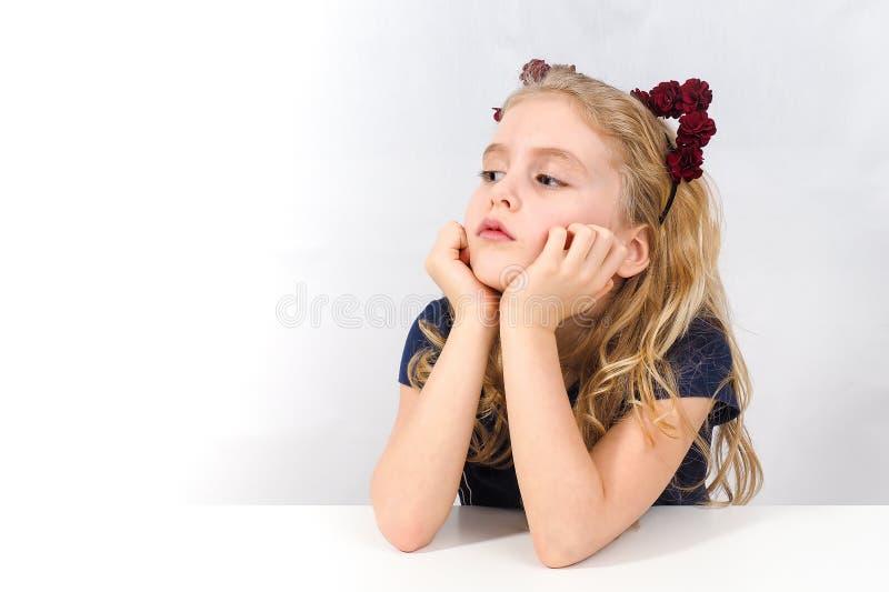Uttråkad liten flicka som sitter på tabellen royaltyfri fotografi