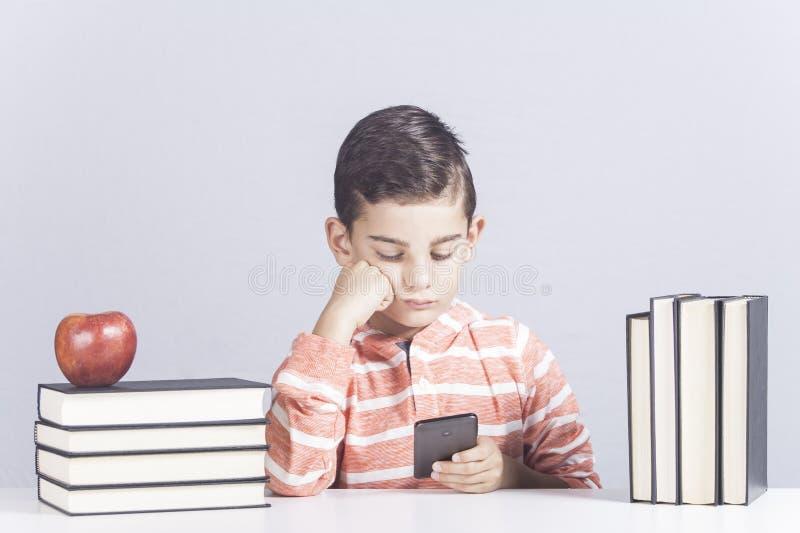 Uttråkad liten skolpojke royaltyfri bild