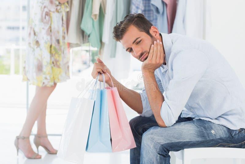 Uttråkad man med shoppingpåsar, medan kvinnan vid kläder rack royaltyfri foto