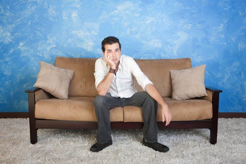 Uttråkad man på sofaen royaltyfri foto