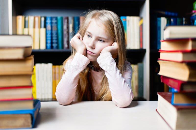 Uttråkad och trött skolflicka som studerar med en hög av böcker royaltyfri fotografi