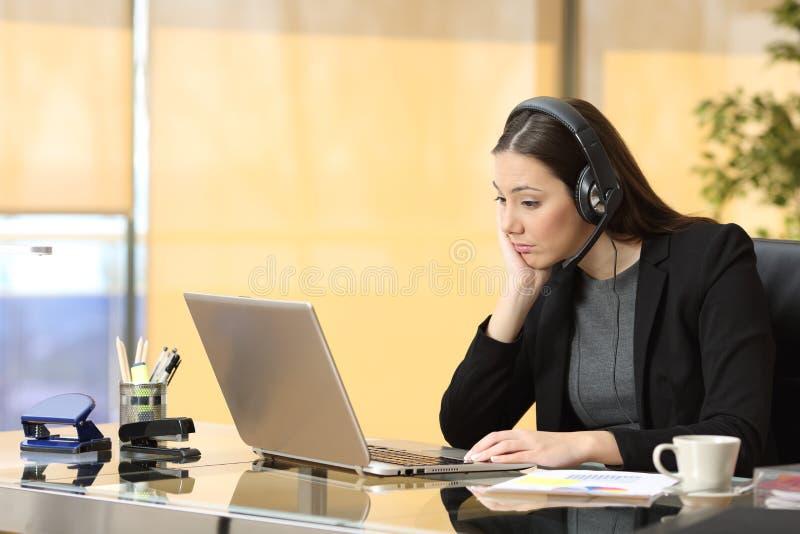 Uttråkad operatör som arbetar på kontoret arkivbilder