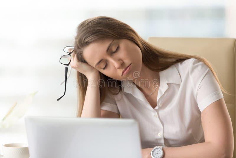 Uttråkad sömnig affärskvinna som till hälften sovande sitter på arbetsplatsen, bor royaltyfri fotografi