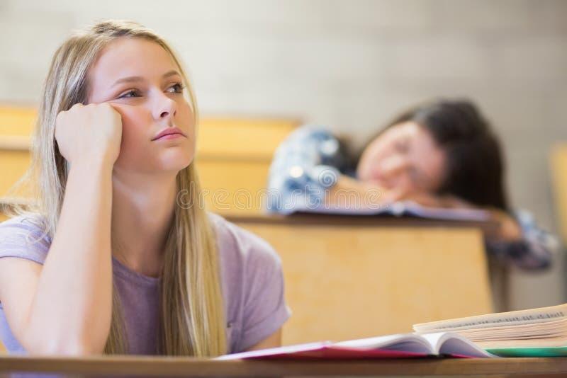 Uttråkad student som lyssnar medan sova för klasskompis arkivbilder