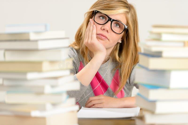 Uttråkad studentflicka mellan bunten av böcker royaltyfri fotografi