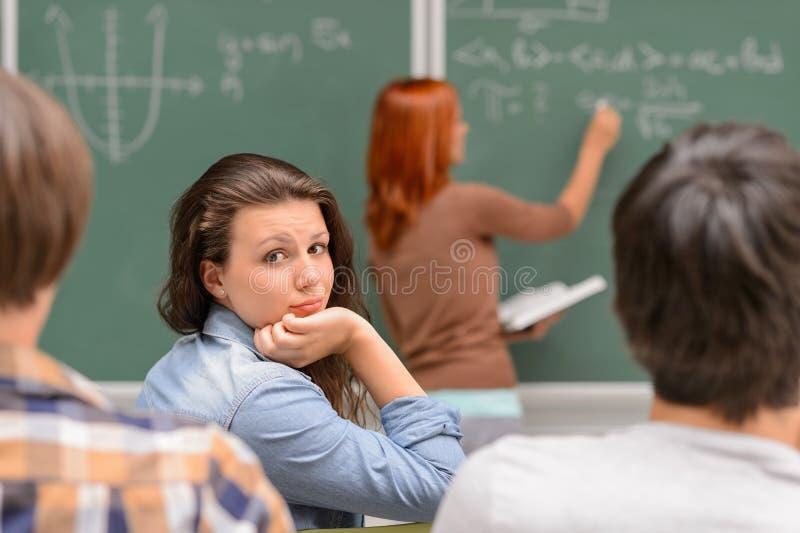 Uttråkad studentflicka under matematikkurs arkivbild