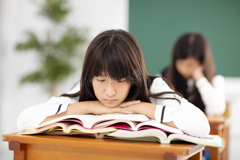 uttråkad tonåringstudent som vilar på bunt av b royaltyfri fotografi