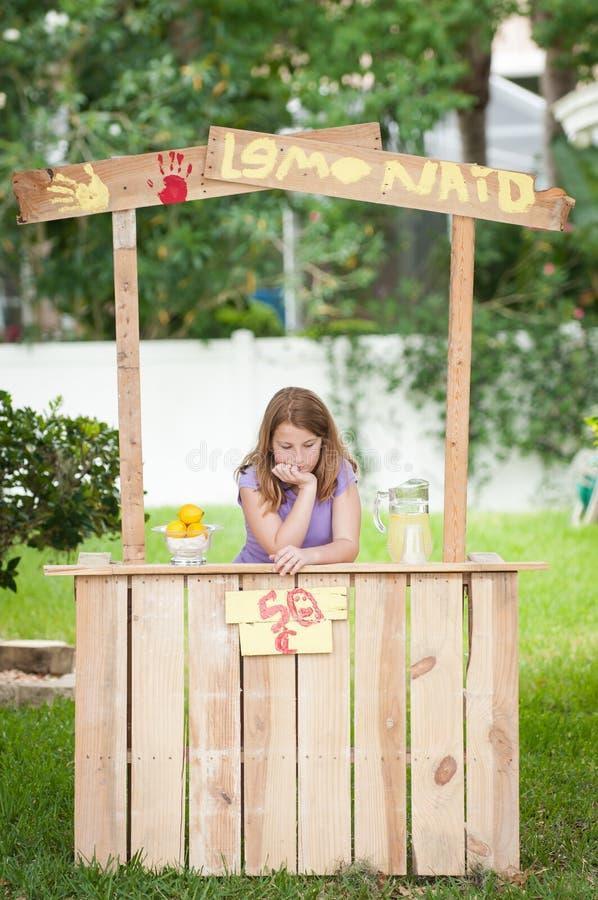 Uttråkad ung flicka med inga kunder på hennes lemonadställning arkivfoton