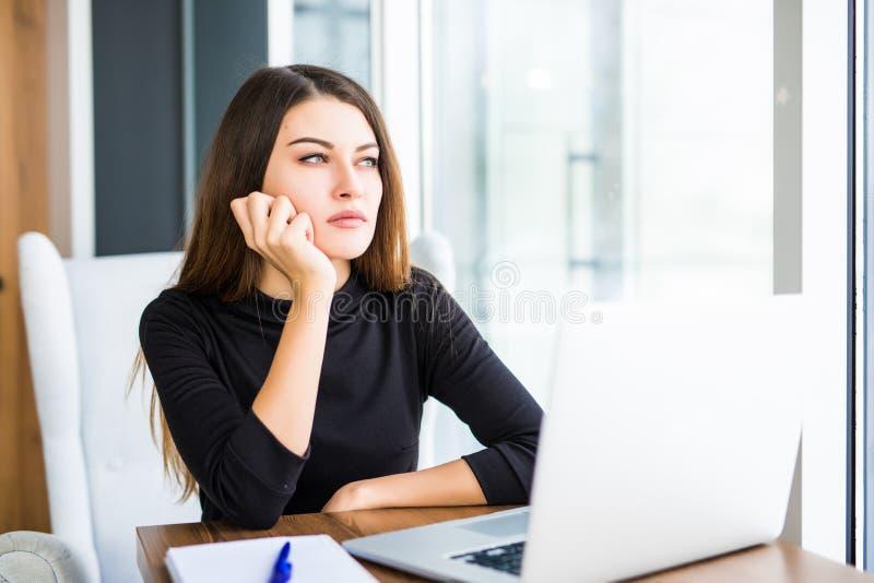 Uttråkad ung kvinna i kontoret som arbetar med en bärbar dator royaltyfri fotografi