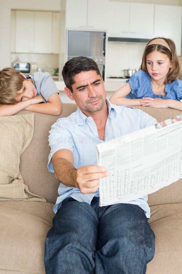 Uttråkade barn som ser den läs- tidningen för fader royaltyfri foto