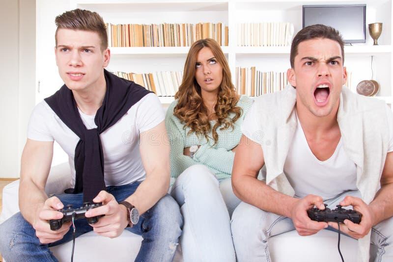 Uttråkade kvinnor mellan två tillfälliga passionerade män som spelar videospelet arkivbilder