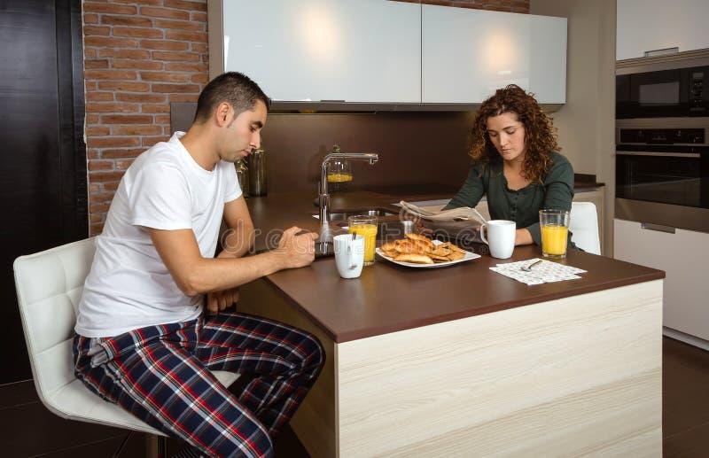Uttråkade par som har frukosten i köket royaltyfri bild