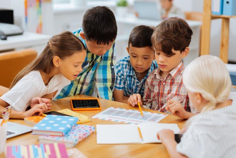 Uttråkade ungar som tillsammans kontrollerar alla olika övningar royaltyfria bilder