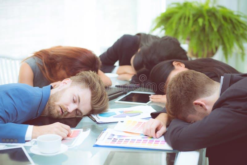 Uttråkat affärsfolk som sover i en mötekollega royaltyfri bild