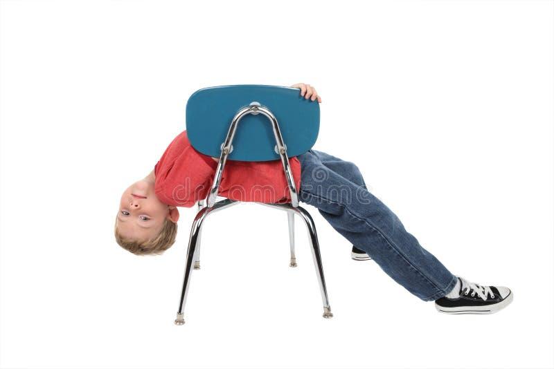 Uttråkat barn som lägger på stol royaltyfri bild