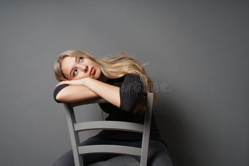 Uttråkat kvinnligt sammanträde grensle på stol och att stirra på taket royaltyfri fotografi